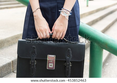 Body and hands of cute Asian Thai high schoolgirls student in school uniform holding black leather bag in education fashion concept