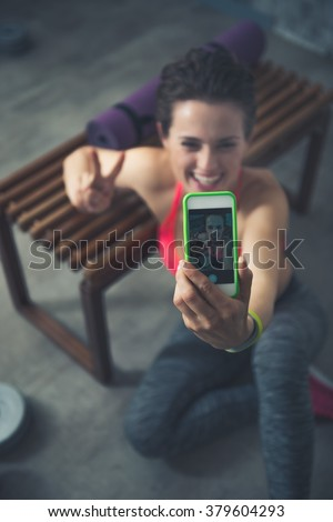 Body and mind workout in loft fitness studio. Closeup on smiling fitness woman sitting in loft gym and taking selfies