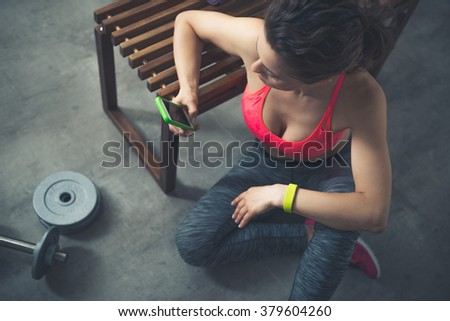 Body and mind workout in loft fitness studio. Fitness woman sitting in loft gym with cell phone - stock photo