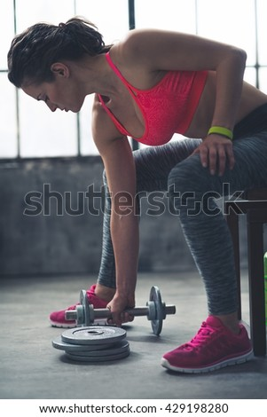 Body and mind workout in loft fitness studio. Fitness woman taking dumbbell from the floor in urban loft gym - stock photo