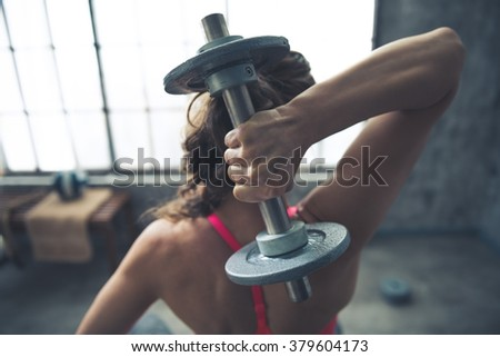 Body and mind workout in loft fitness studio. Seen from behind fitness woman lifting dumbbell