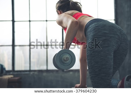 Body and mind workout in loft fitness studio. Seen from behind fitness woman lifting dumbbell in loft gym - stock photo