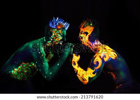 Body art glowing in ultraviolet light,  four elements, Earth against Fire - stock photo