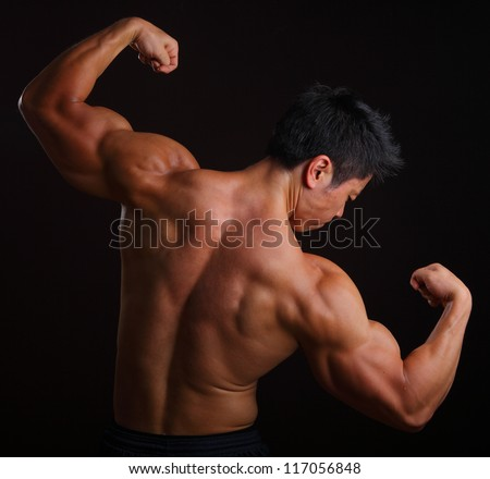 Body Builder posing with his back muscles on black background - stock photo