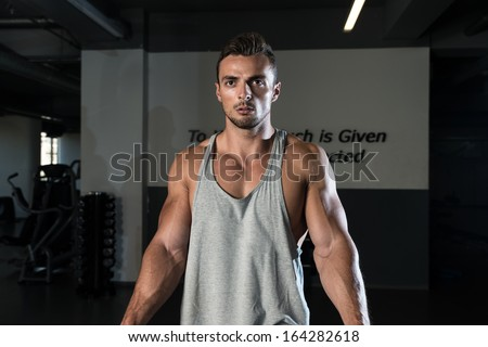 Body Builder Workout On Cable Machine. Standing Low Pulley Deltoids Raise - stock photo