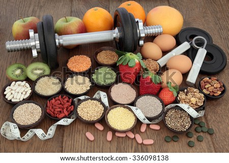 Body building dumbbells and hand grippers with health and super food selection including supplement powders  and fresh fruit with tape measure over oak background. - stock photo