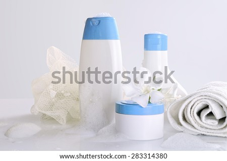 body care and beauty products in white and blue containers on a white table glass in a bathroom with foam. Front view. Isolated. - stock photo