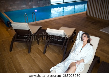 Body care and pampering in hotel luxury spa.Woman lying on the deckchair by swimming pool in resort.Wellness concept.Woman in bathrobe enjoying her time in hotel.Grain added - stock photo