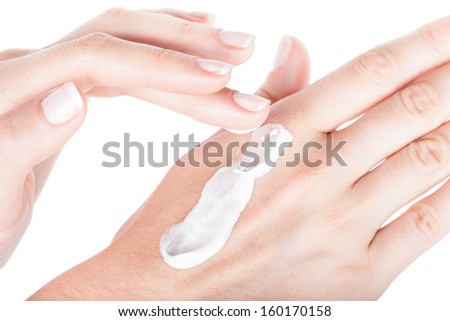 Body Care. Applying hand moisturiser cream on female hands, closeup isolated on white