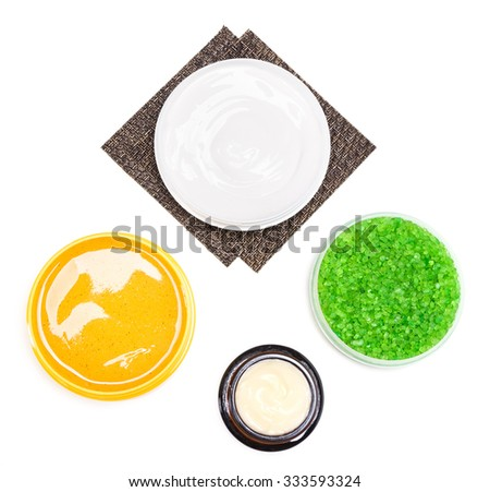 Body care cosmetic products: bath sea salt, jars filled with creams and natural body scrub on white background, top view. Spa and pampering cosmetics - stock photo
