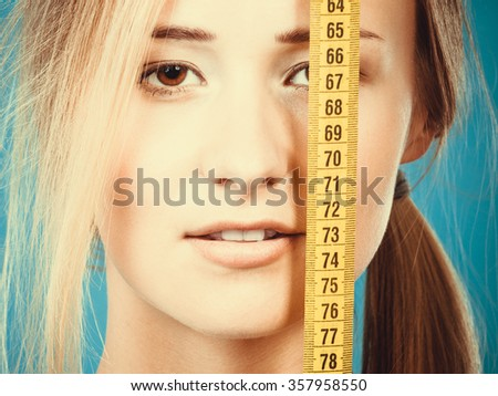 Body care diet and weight loss concept. Fitness girl sporty woman covering her eye with measuring tape, measuring her body - stock photo