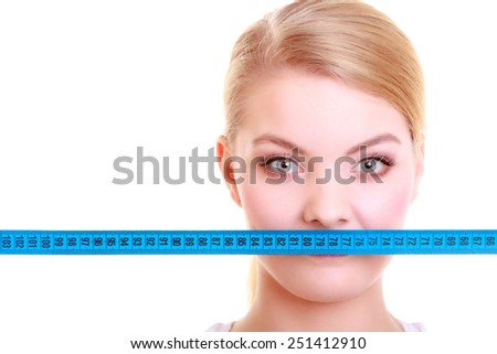 Body care diet and weight loss concept. Fitness girl sporty woman covering her mouth lips with measuring tape isolated on white - stock photo