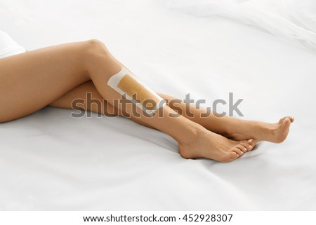 Body Care. Long Woman's Legs With Wax Strip On. Beautiful Female Depilates Her Sexy Slender Long Legs By Waxing For Perfect Hairless Smooth And Silky Skin. Epilation Hair Removal, Beauty Concept