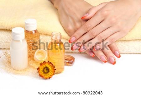 Body care: orange fingernails, yellow bottles and towels - stock photo