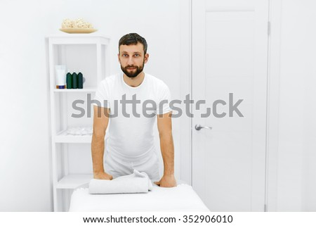 Body Care. Portrait Of Masseur Standing By Massage Table In Spa Salon. Physical Therapist In Medical Office. Beauty Treatment, Massage Therapy. Healthcare, Medicine Concept. Wellness, Lifestyle. - stock photo