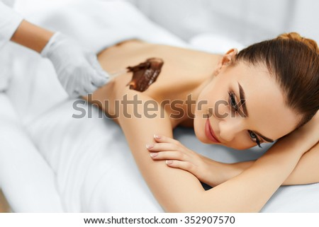 Body Care. Spa Treatment. Portrait Of Beautiful Smiling Young Woman Receiving Cosmetic Chocolate Body Mask At Beauty Salon. Skin Care. Healthy Lifestyle