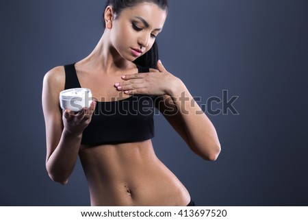 Body care. Studio shot of beautiful young woman with dark brown hair. Woman using body cream - stock photo