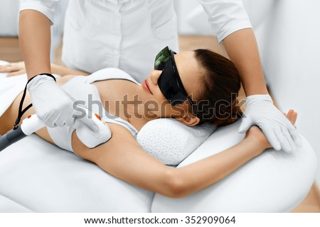 Body Care. Underarm Laser Hair Removal. Beautician Removing Hair Of Young Woman's Armpit. Laser Epilation Treatment In Cosmetic Beauty Clinic. Hairless Smooth And Soft Skin. Health And Beauty Concept. - stock photo