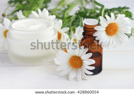 Body cream white essential oil, chamomile daisy flowers. Herbal cosmetic products. Soft focus. - stock photo