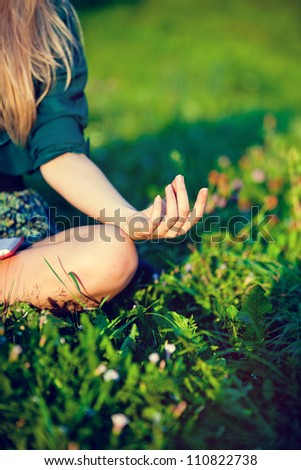 Body of a beautiful girl in a meditation in the lotus position on the grass in the park - stock photo