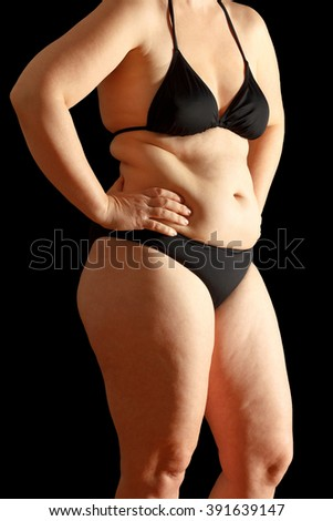 Body of a middle aged woman in bikini with excessive fat on waist and thighs, dimpled skin, black background