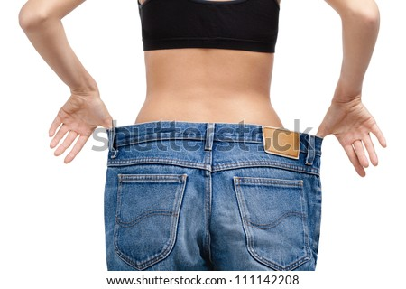 Body of a slim girl wearing enormous jeans, isolated on white - stock photo