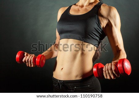 Body of a young fit woman lifting dumbbells on dark background - stock photo