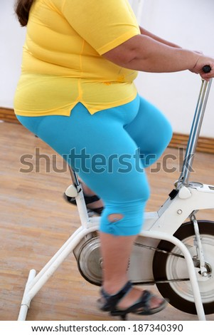 body of overweight woman exercising on bike simulator  - stock photo