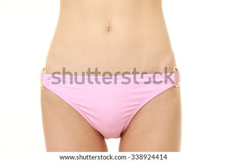 Body of young woman in a pink bikini - stock photo