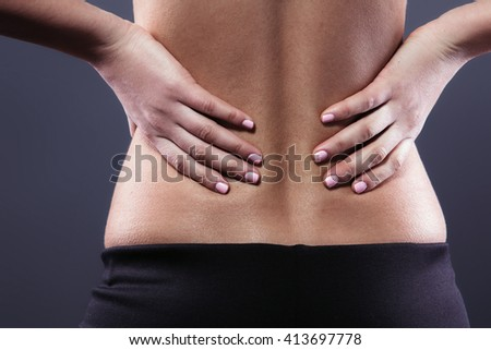 Body pain. Close up studio shot of woman. Woman suffering from backache