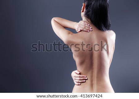 Body pain. Studio shot of beautiful young woman with dark brown hair. Woman suffering from backache