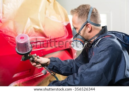 Body painter spraying paint on car to renew the varnish - stock photo