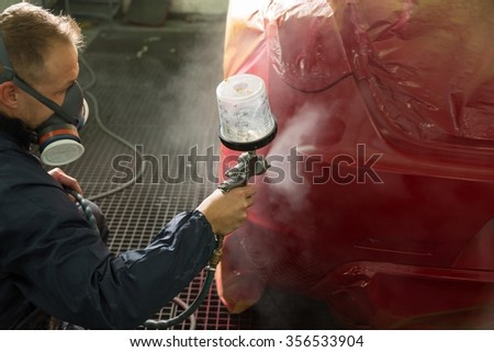 Body painter with airgun spraying paint on a car - stock photo
