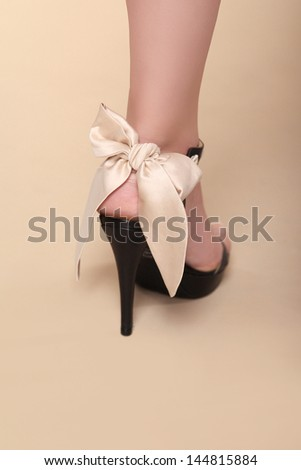Body part. Fashion shoe over beige background. Studio Photo - stock photo