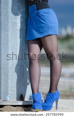 Body part of woman's legs posing in subway station outside with sunset light, wearing stocking , blue skirt and high heels
