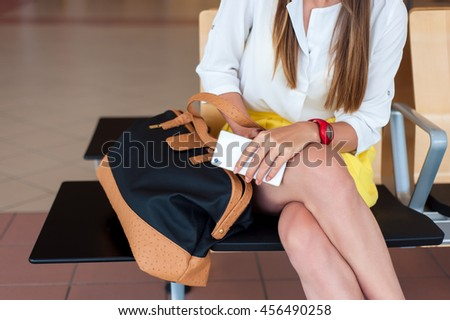 Body parts close-up. Young woman holding her cell phone while sitting, waiting to board a plane at the departure gates.  - stock photo