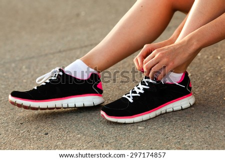 body parts of runner woman tying laces at sunset