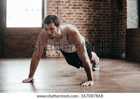 Body power. Confident muscled young man wearing sport wear and doing push-ups while exercising on the floor in loft interior - stock photo