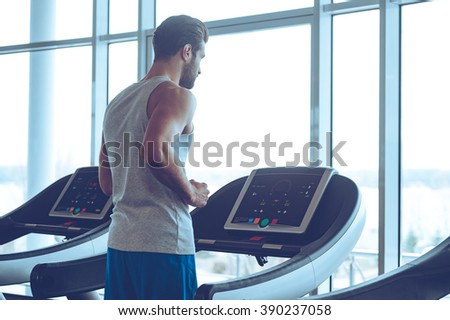 Body power. Young man in sportswear running on treadmill in front of window at gym - stock photo