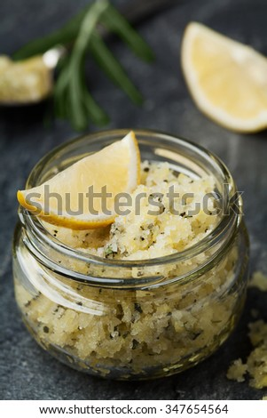 Body scrub of sea salt with lemon, rosemary and olive oil in glass jar on stone table, homemade cosmetic for Spa care - stock photo