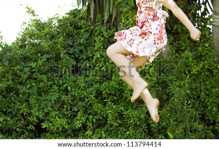 Body section of a young girl jumping in the air in a green garden space. - stock photo