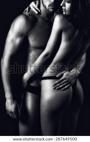 Body sexy couple on beach topless at sunset. Low light.  - stock photo