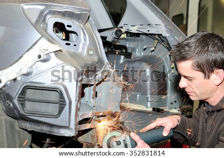 Body shop worker grinding car panel. - stock photo