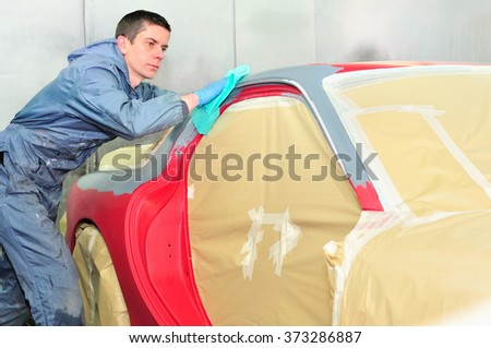 Body worker preparing car surface for paint.