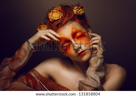 Bodyart. Imagination. Artistic Woman with Red - Gold Makeup and Flowers. Coloring - stock photo