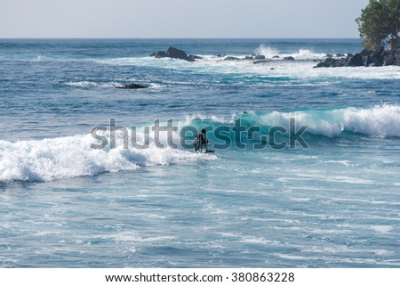 Bodyboarding and surfing in the waves of the Atlantic in front of the island La Gomera. A short light type of surfboard ridden in a prone position - stock photo