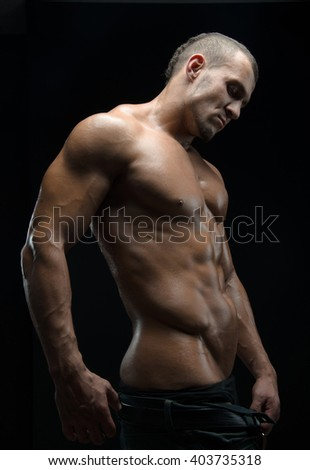 Bodybuilder and strip theme: beautiful with pumped muscles naked man posing in the studio on a dark background - stock photo