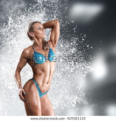 Bodybuilder athletic woman in bikini showing her muscles - stock photo