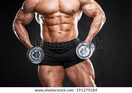 Bodybuilder. Bodybuilder using dumbbell, isolated on black - stock photo