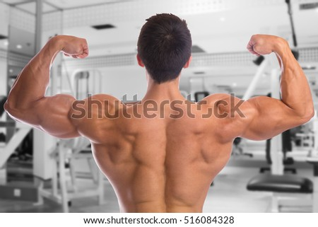 Bodybuilder bodybuilding flexing muscles posing gym back biceps strong muscular young man fitness studio